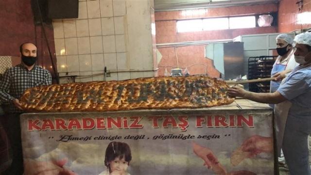 Kilolarca hamurdan yapılan 2 metrelik 'Evde Kal Türkiye' yazılı pide açık artırmayla satıldı.